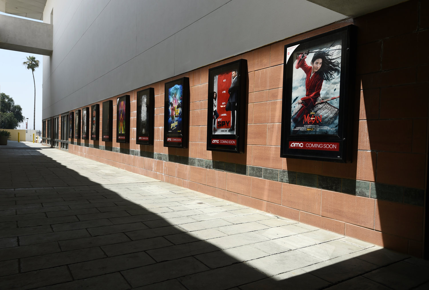 FILE - Posters for upcoming movies are displayed in an empty corridor at the currently closed AMC Burbank Town Center 8 movie theaters complex on April 29, 2020, in Burbank, Calif. After several false starts, the film industry is hoping to bring new releases back into movie theaters in late August. But for blockbusters, it may mean rethinking opening weekend and returning to a more gradual rollout through international and U.S. territories. Gone for now are the days of massive global openings. And theater owners say if they don't get new films soon, they may not make it to 2021. (AP Photo/Chris Pizzello, File)