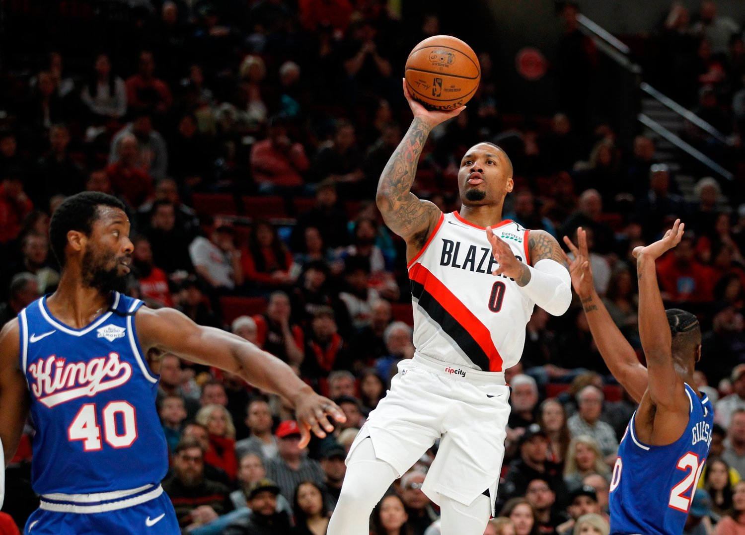 In this Saturday, March 7, 2020, file photo, Portland Trail Blazers guard Damian Lillard, center, shoots as Sacramento Kings forward Harrison Barnes, left, and forward Harry Giles III, right, defend during the first half of an NBA basketball game in Portland, Ore. Lillard says he will spend most of his downtime working on recording music while inside the NBA bubble. (AP Photo/Steve Dipaola, File)