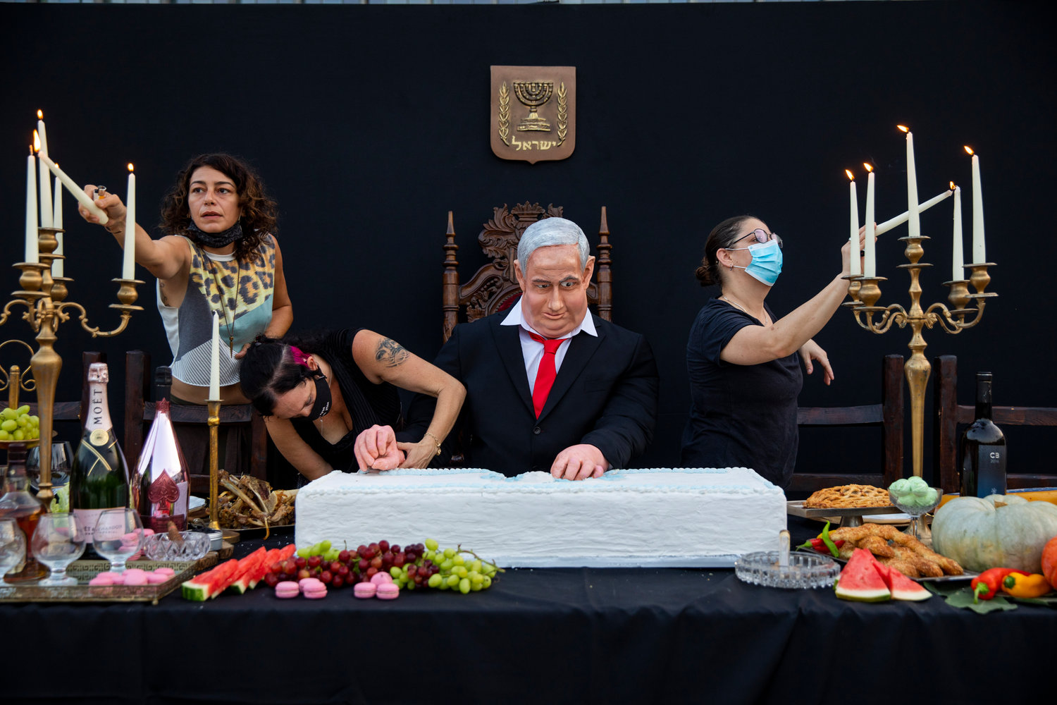 "Team members of Israeli artist Itay Zalait, work on an installation depicting Prime Minister Benjamin Netanyahu at a mock ""Last Supper"" at Rabin square in Tel Aviv, Israel, Wednesday, July 29, 2020. The installation, placed in a central Tel Aviv square on Wednesday, in the latest twist in a summer of protests against Netanyahu and his lengthy rule. (AP Photo/Oded Balilty)"