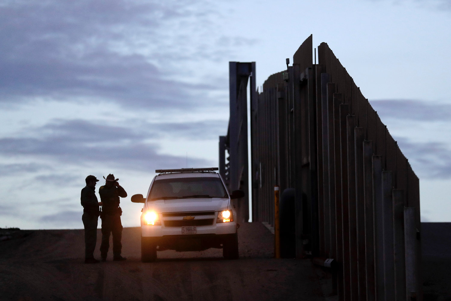 In this Nov. 21, 2018 file photo, United States Border Patrol agents stand by a vehicle near one of the border walls separating Tijuana, Mexico and San Diego, in San Diego. As of this week, the ACLU has filed nearly 400 lawsuits and other legal actions against the Trump administration, some meeting with setbacks but many resulting in important victories. Of the lawsuits, 174 have dealt with immigrant rights, targeting the family separation policy, detention and deportation practices, and the administration's repeated attempts to make it harder to seek asylum at the U.S.-Mexico border.  (AP Photo/Gregory Bull, File)