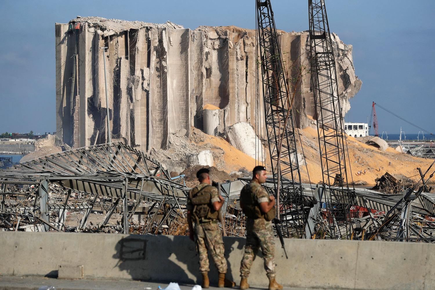 Lebanese army soldiers stand guard at the scene where an explosion hit on Tuesday the seaport of Beirut, Lebanon, Thursday, Aug. 6, 2020. (AP Photo/Hussein Malla)..