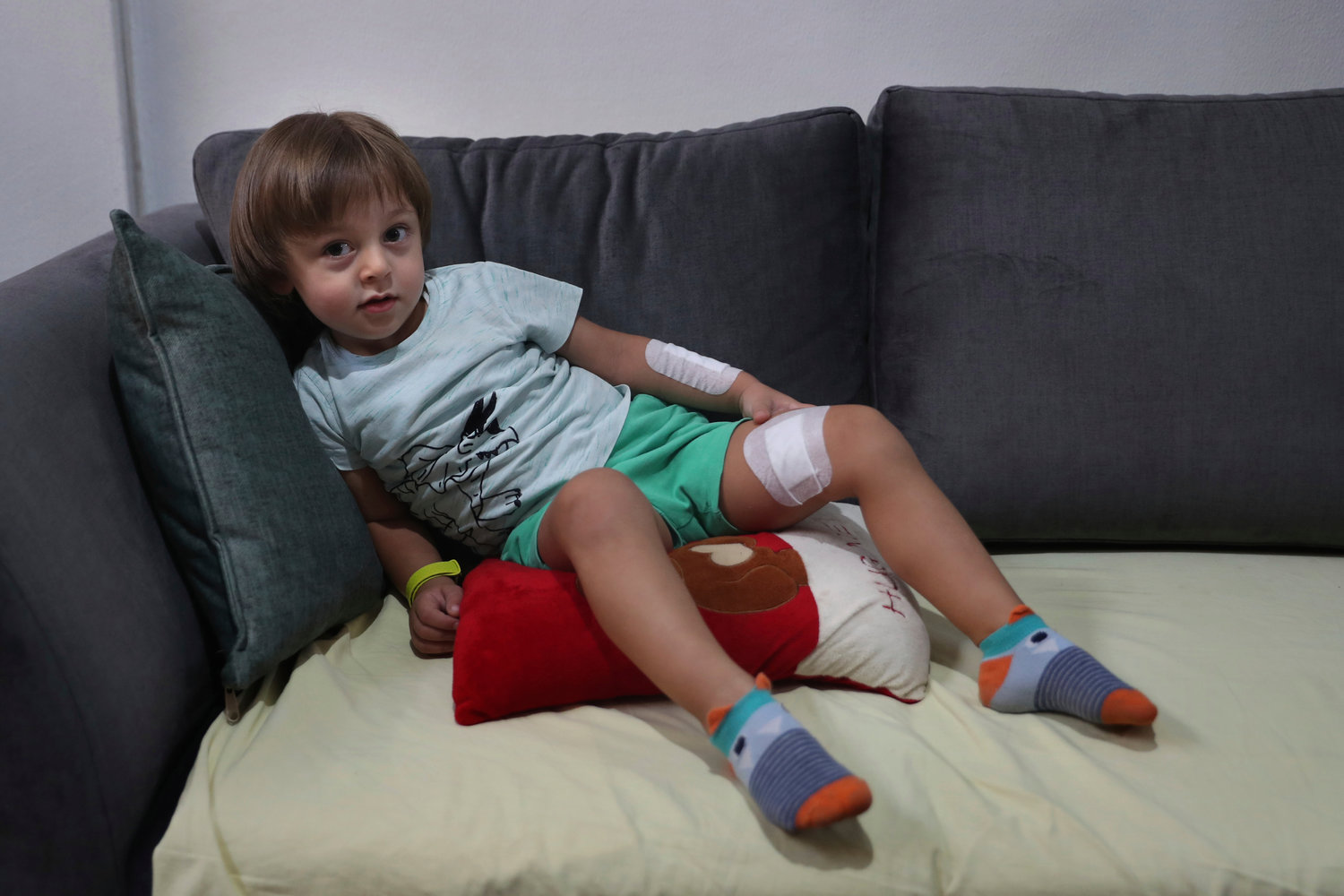 Three-year-old Abed Itani lies on a sofa at his family house in Beirut, Lebanon, Tuesday, Aug. 11, 2020. Abed was playing with his Lego blocks when the huge blast ripped through Beirut, shattering the nearby glass doors. He had cuts on his tiny arms and feet, a head injury, and was taken to the emergency room, where he sat amid other bleeding people. (AP Photo/Bilal Hussein)