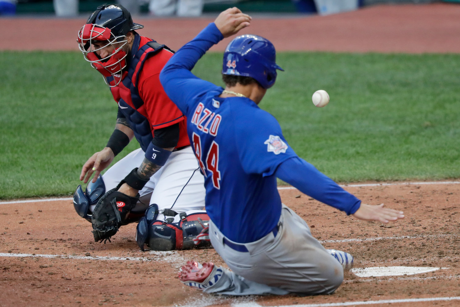 Chicago Cubs' Anthony Rizzo, right, scores as Cleveland Indians catcher Sandy Leon can't hold onto the ball in the fifth inning in a baseball game, Wednesday, Aug. 12, 2020, in Cleveland. (AP Photo/Tony Dejak)