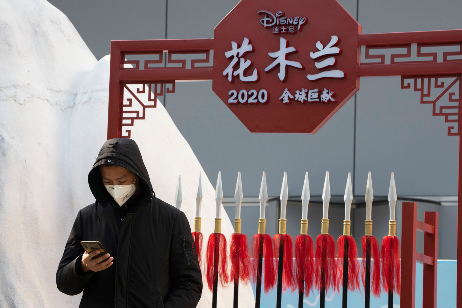 "A man wearing a mask to protect from the coronavirus watch over a set promoting the Disney movie Mulan in.Beijing on Wednesday, Feb. 19, 2020. Disney is under fire for partially filming its live-action reboot ""Mulan"" in Xinjiang, the region in China where the Chinese government has been running mass internment camps for Uyghurs and other Muslim minorities. (AP Photo/Ng Han Guan)"