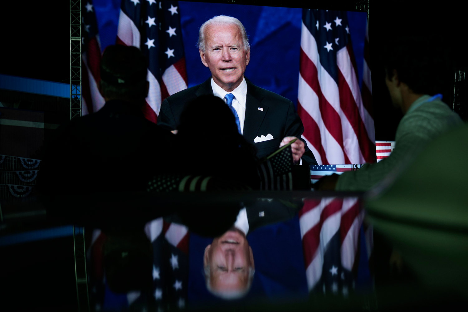 Supporters watch the program outside the venue where Democratic presidential candidate former Vice President Joe Biden is speaking, during the final day of the Democratic National Convention, Thursday, Aug. 20, 2020, at the Chase Center in Wilmington, Del. (AP Photo/Carolyn Kaster)