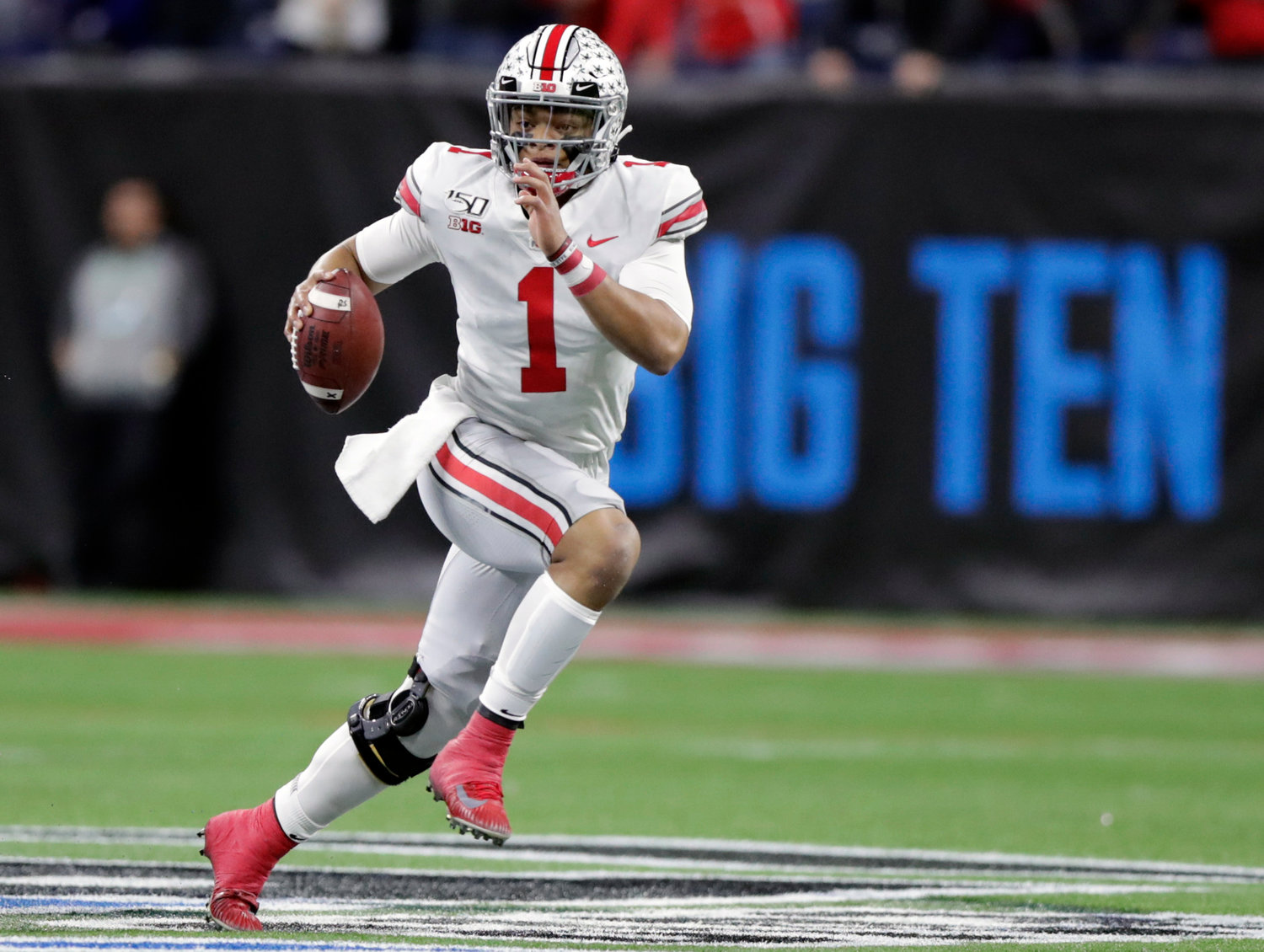 Ohio State quarterback Justin Fields (1) runs with the ball past Wisconsin defensive end Isaiahh Loudermilk during the first half of the Big Ten championship NCAA college football game, Saturday, Dec. 7, 2019, in Indianapolis. (AP Photo/Michael Conroy)