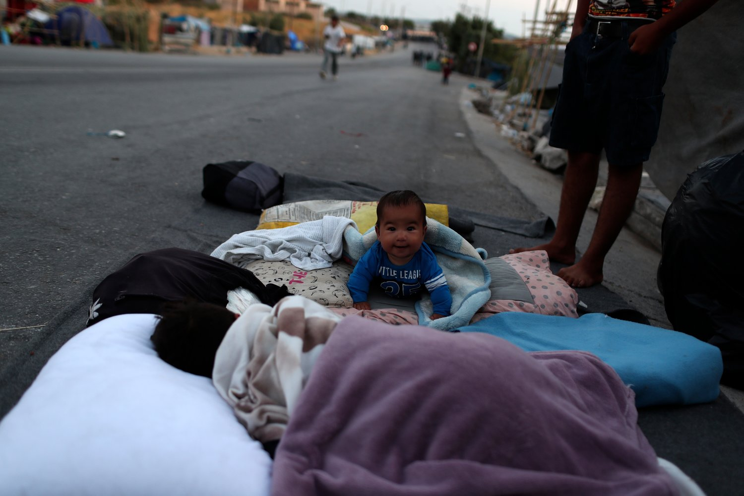 A baby crawls as migrants remained camped out on a road leading from Moria to the capital of Mytilene, on the northeastern island of Lesbos, Greece, Thursday, Sept. 17, 2020. Fires swept through the overcrowded camp at Moria on two nights last week, prompting more than 12,000 migrants and refugees to flee. Most of them remain without shelter even though emergency tents are available at another island site where a new camp is being built.  (AP Photo/Petros Giannakouris)