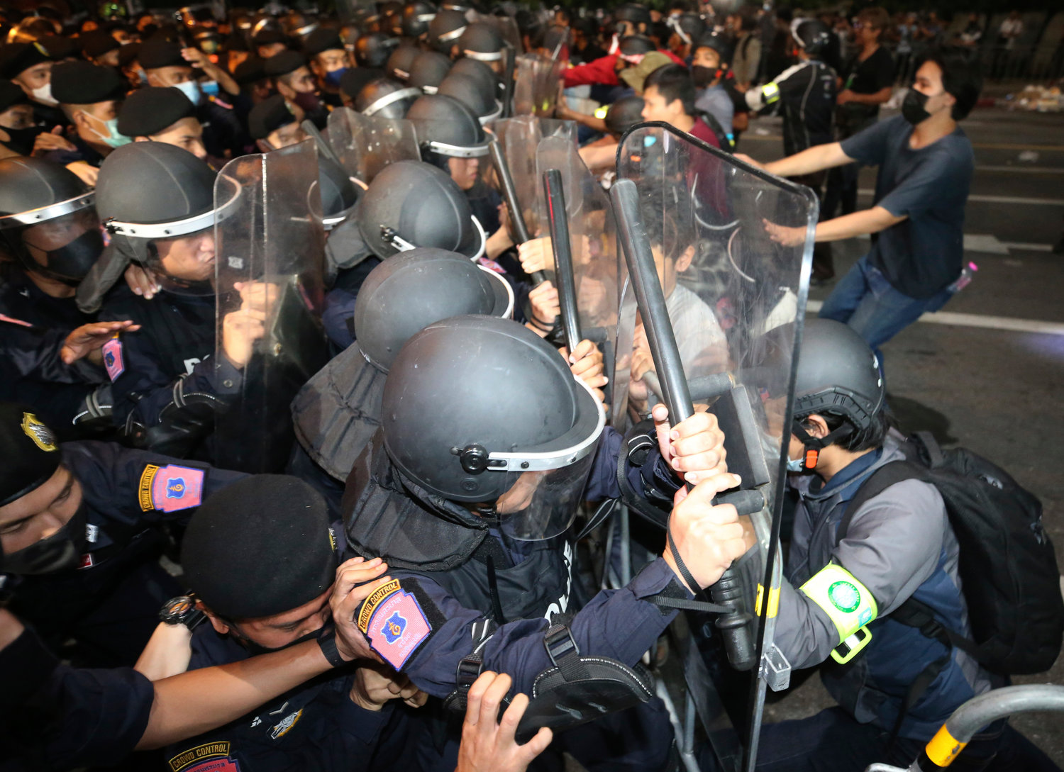 Protesters push Thai policemen with riot shields during demonstration in Bangkok, Thailand, Thursday, Oct. 15, 2020. Thai police dispersed a group of protesters holding an overnight rally outside the office of the Prime Minister. (AP Photo/Rapeephat Sitichailapa).