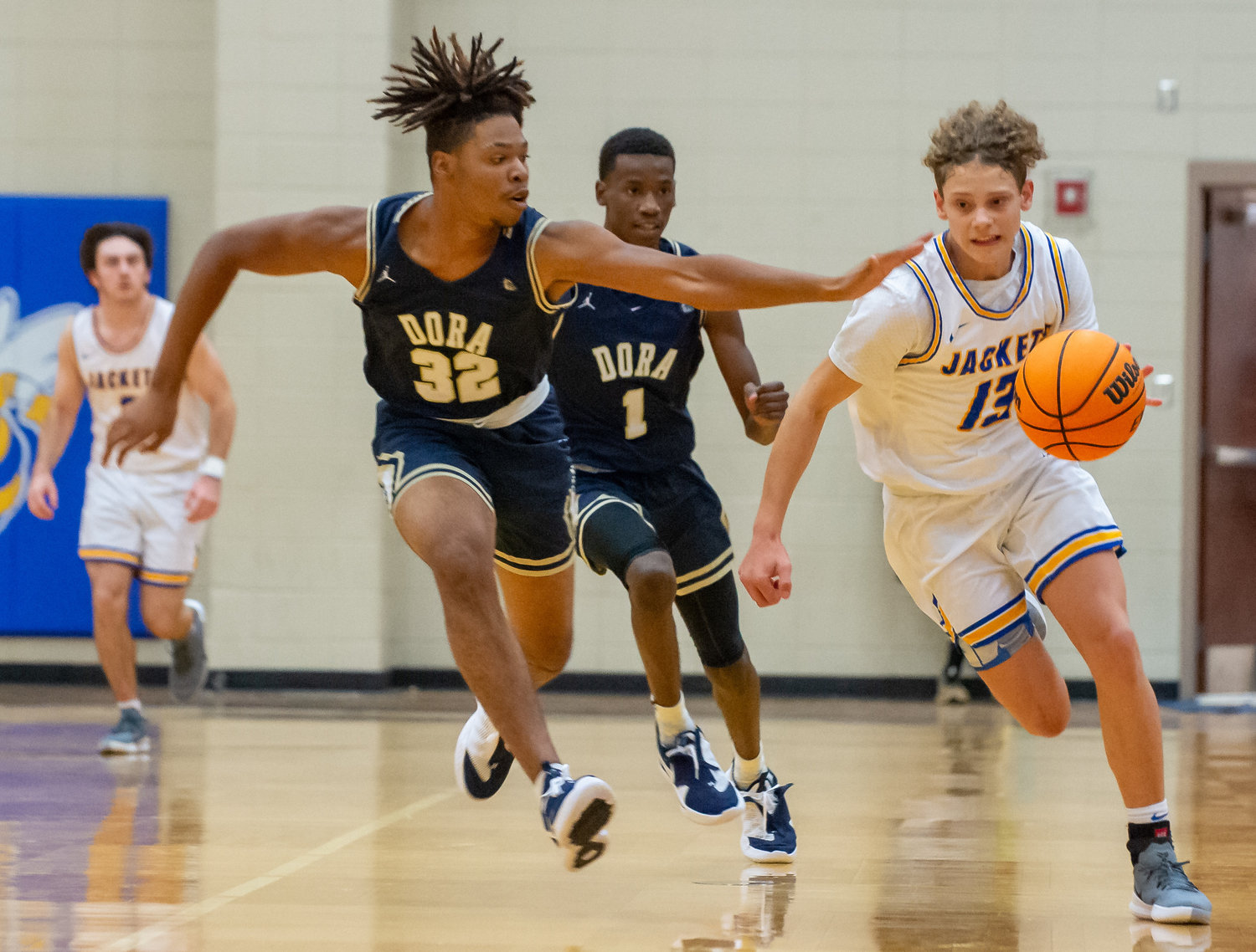 Curry's Jase Calloway (13) brings the ball up the court as Dora's Michael Smoot (32) and Malique Davis (1) defend during their game on Monday night at Curry High School. Curry won 77-61.