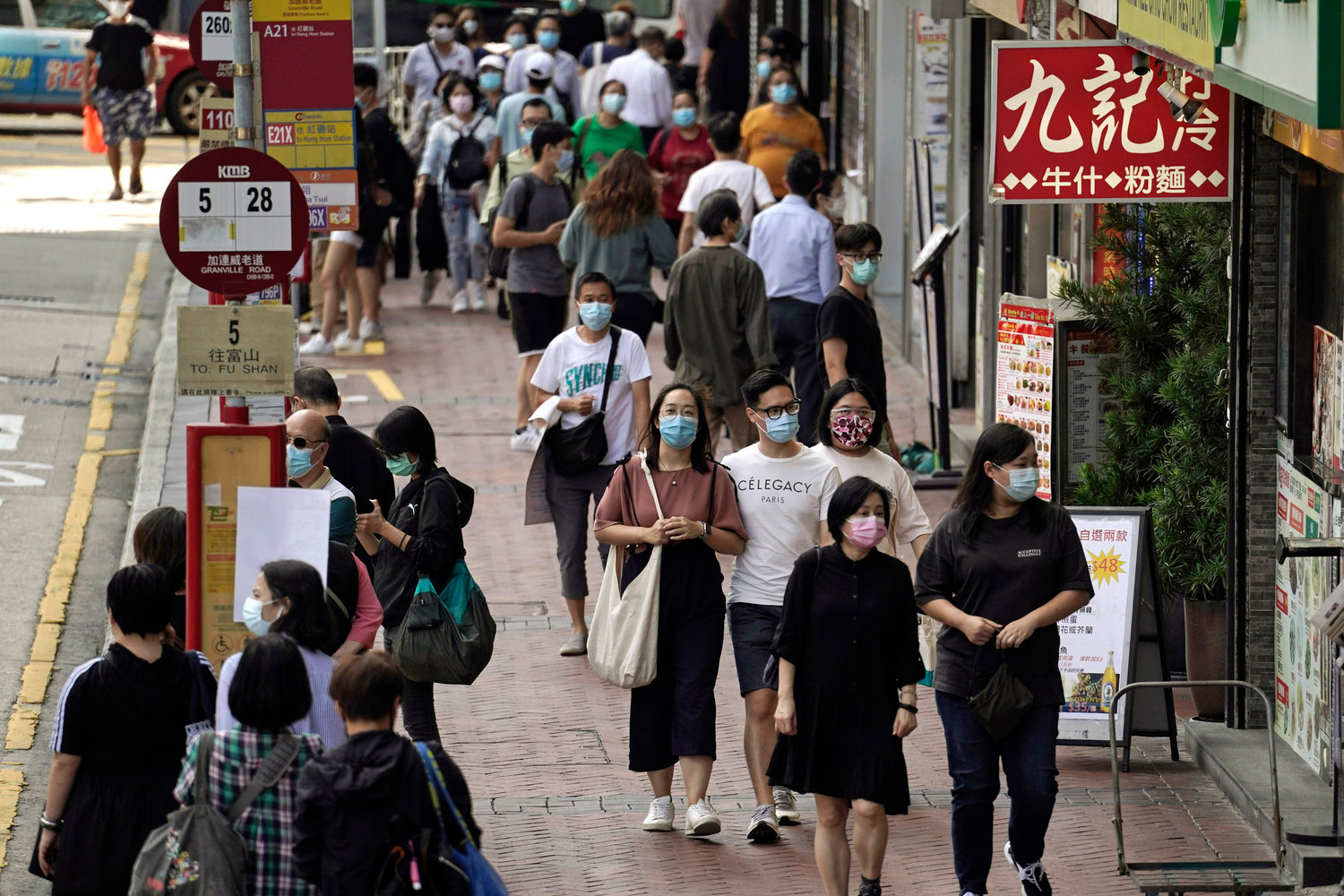 People wearing masks to protect against the coronavirus, walk down a street in Hong Kong, Friday, Oct. 9, 2020. (AP Photo/Kin Cheung)