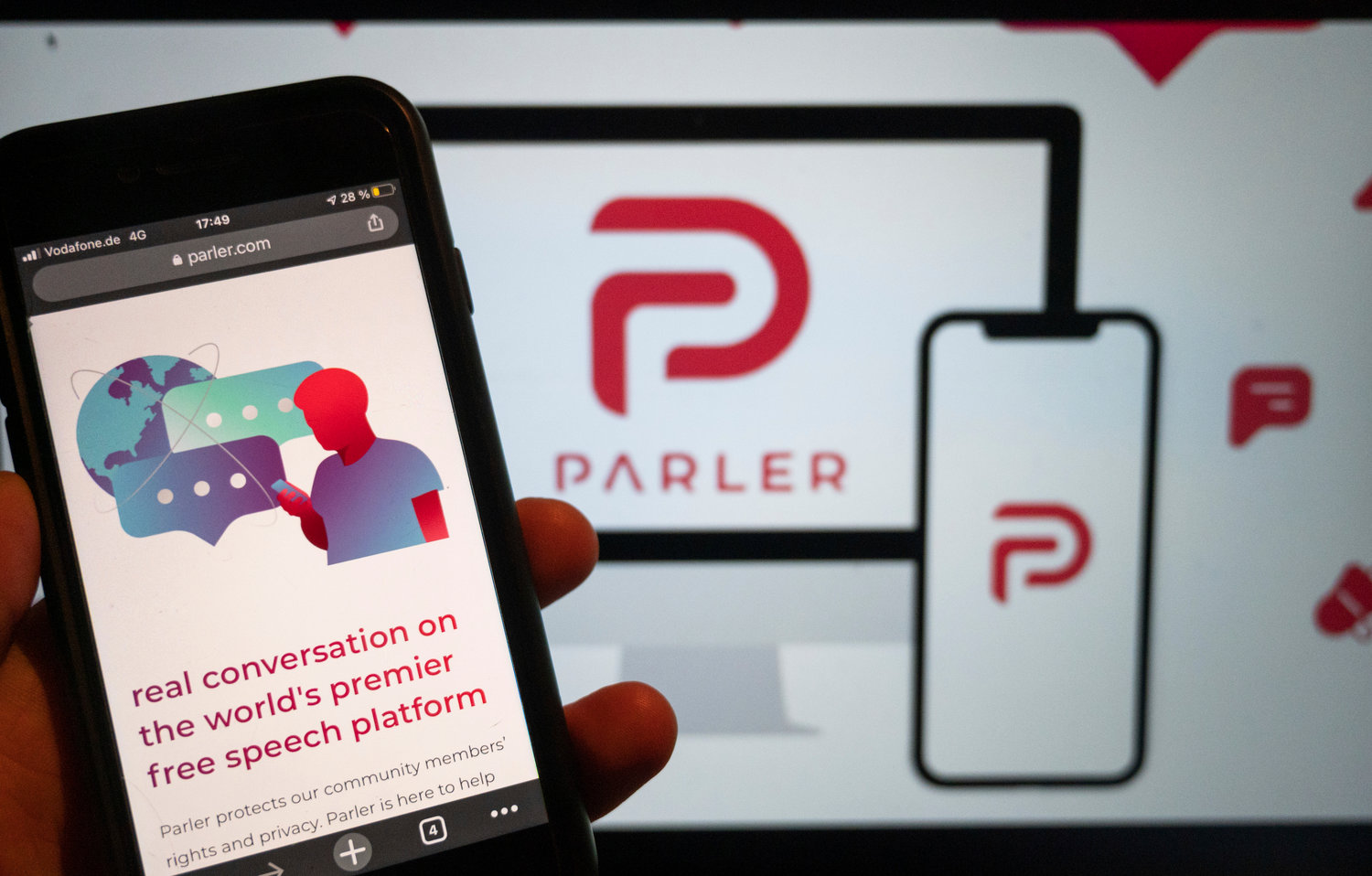 The website of the social media platform Parler is displayed in Berlin, Jan. 10, 2021. The platform's logo is on a screen in the background. The conservative-friendly social network Parler was booted off the internet Monday, Jan. 11, over ties to last week's siege on the U.S. Capitol, but not before hackers made off with an archive of its posts, including any that might have helped organize or document the riot. (Christophe Gateau/dpa via AP)
