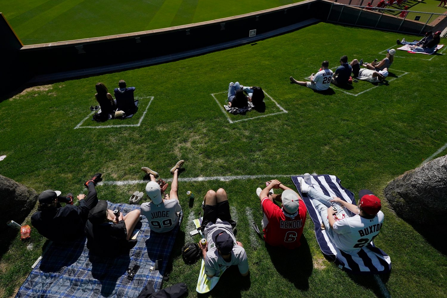 Fans sit in their COVID-19 socially-distanced pods at the Goodyear Ballpark during the fourth inning of a spring training baseball game between the Cleveland Indians and the Cincinnati Reds, Sunday, Feb. 28, 2021, in Goodyear, Ariz. (AP Photo/Ross D. Franklin)