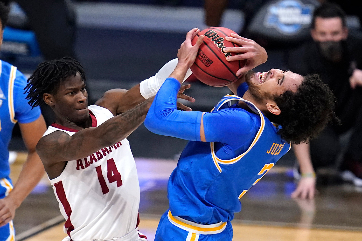 Alabama guard Keon Ellis (14) ties up UCLA guard Johnny Juzang (3) dueing their Sweet 16 game in the NCAA men's college basketball tournament at Hinkle Fieldhouse in Indianapolis on Sunday. UCLA won 88-78 in overtime.