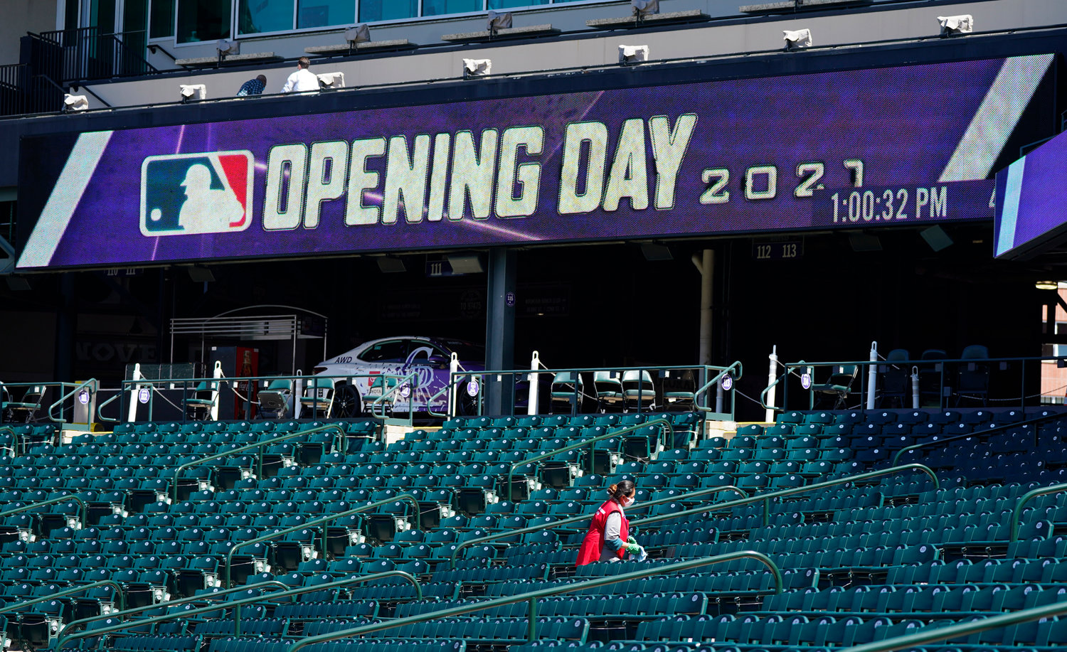 A worker cleans seats to prepare Coors Field for the return of fans in the era of the coronavirus during a news conference Wednesday, March 31, 2021, at the stadium in downtown Denver. A small number of fans were allowed to watch the Rockies go through a workout Wednesday before the team hosts the Los Angeles Dodgers in the squads' season-opener Thursday, April 1. (AP Photo/David Zalubowski).............
