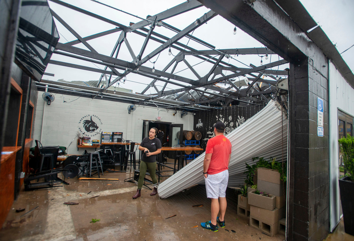 Employees assess the damage after the storm that came through Pensacola, Fla., and blew the roof off of Emerald Republic Brewing on Saturday, April 10, 2021.