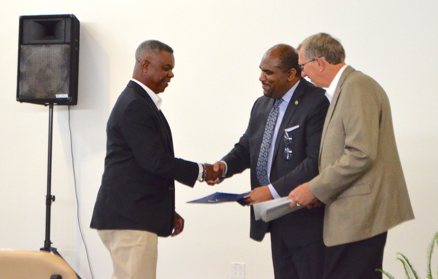 HVAC Fast Track graduate Cedric C. Davis receives a certificate for completing the program.