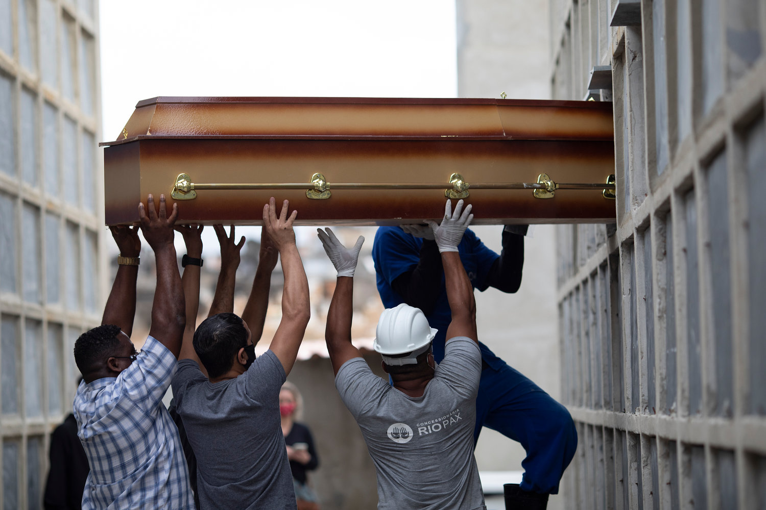 FILE - In this April 13, 2021, file photo, the remains of a woman who died from complications related to COVID-19 are placed into a niche by cemetery workers and relatives at the Inahuma cemetery in Rio de Janeiro, Brazil. The global death toll from the coronavirus topped a staggering 3 million people Saturday, April 17, 2021, amid repeated setbacks in the worldwide vaccination campaign and a deepening crisis in places such as Brazil, India and France. (AP Photo/Silvia Izquierdo, File)
