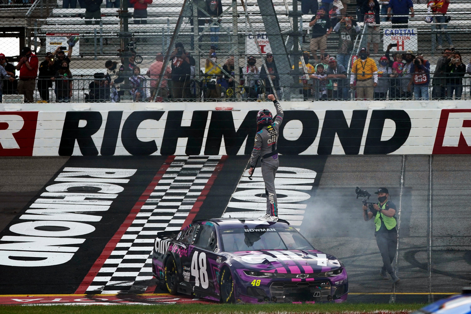Alex Bowman (48) stands on his car as he celebrates winning the NASCAR Cup Series auto race at Richmond International Raceway in Richmond, Va., Sunday, April 18, 2021.  (AP Photo/Steve Helber)