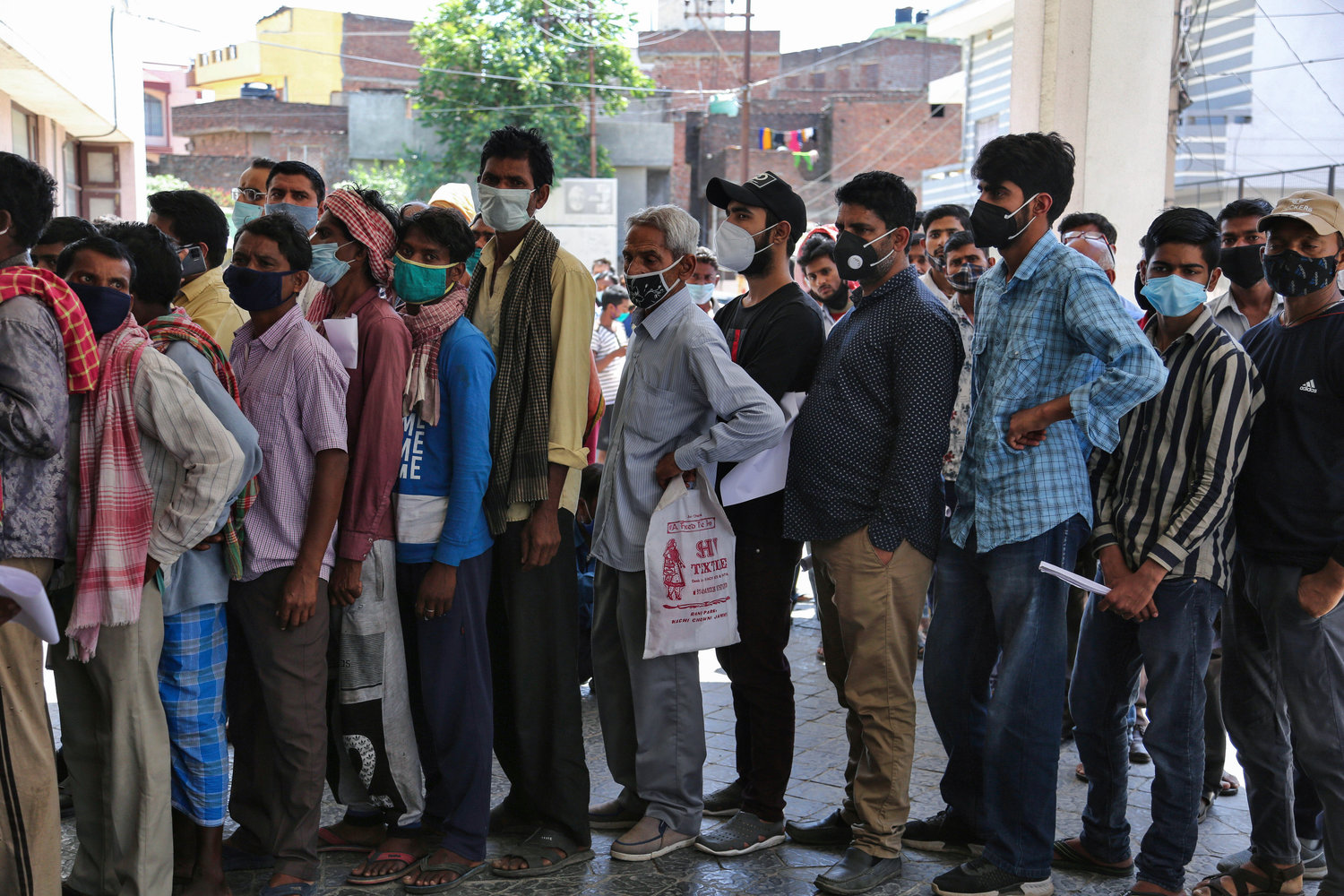 People wearing face masks as a precaution against the coronavirus wait to test for COVID-19 (no social distancing) at a government hospital in Jammu, India, Monday, April.19,2021.The government has decided to close all educational institutions till May 15.(AP Photo/Channi Anand)