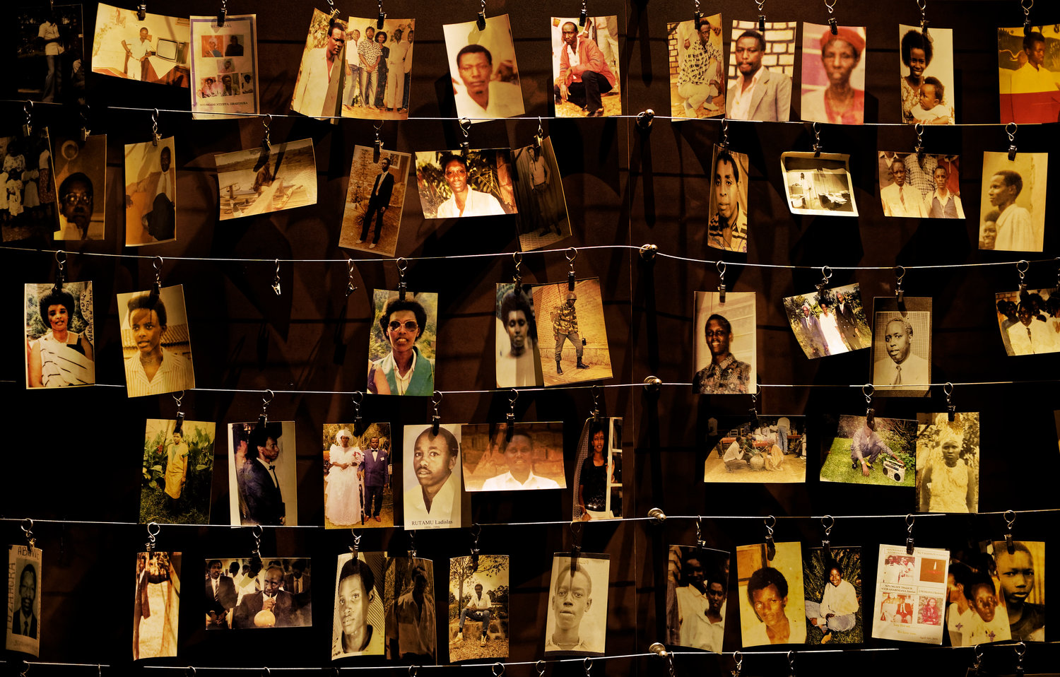 "FILE - In this Friday, April 5, 2019 file photo, family photographs of some of those who died hang on display in an exhibition at the Kigali Genocide Memorial centre in the capital Kigali, Rwanda. A report commissioned by the Rwandan government due to be made public on Monday, April 19, 2021 concludes that the French government bears ""significant"" responsibility for ""enabling a foreseeable genocide"" that left more than 800,000 dead in 1994 and that that France ""did nothing to stop"" the massacres. (AP Photo/Ben Curtis, File)"
