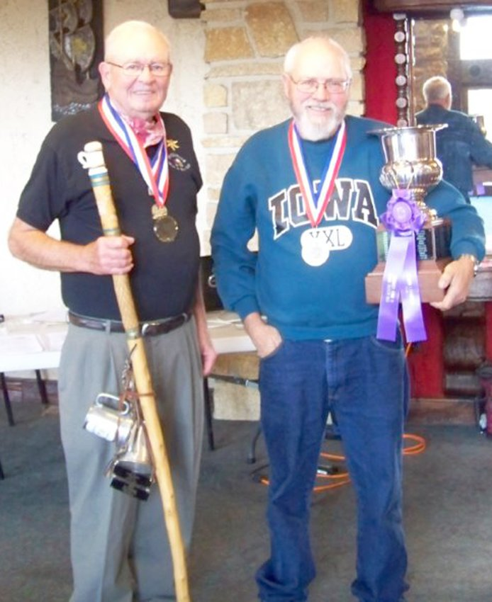 Don Thompson of Dunlap, left, is pictured with the Walking Stick that was carved back in 1994 by Phil Rickert of Santa Fe, N.M., as a traveling trophy to be kept for a year by the Grand Champion Bier Maker. On the right is Don Priebe of Mason City, who is pictured with the Wollenhaup traveling trophy that he can keep for a year for being the Grand Champion Wine Maker.