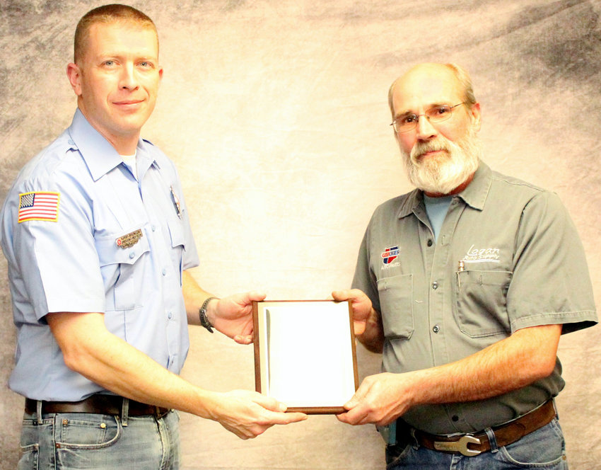 Logan Auto Supply owner Gene Beckner (right) accepts the Business of the Year honor from Fireman of the Kory Brunken (left).