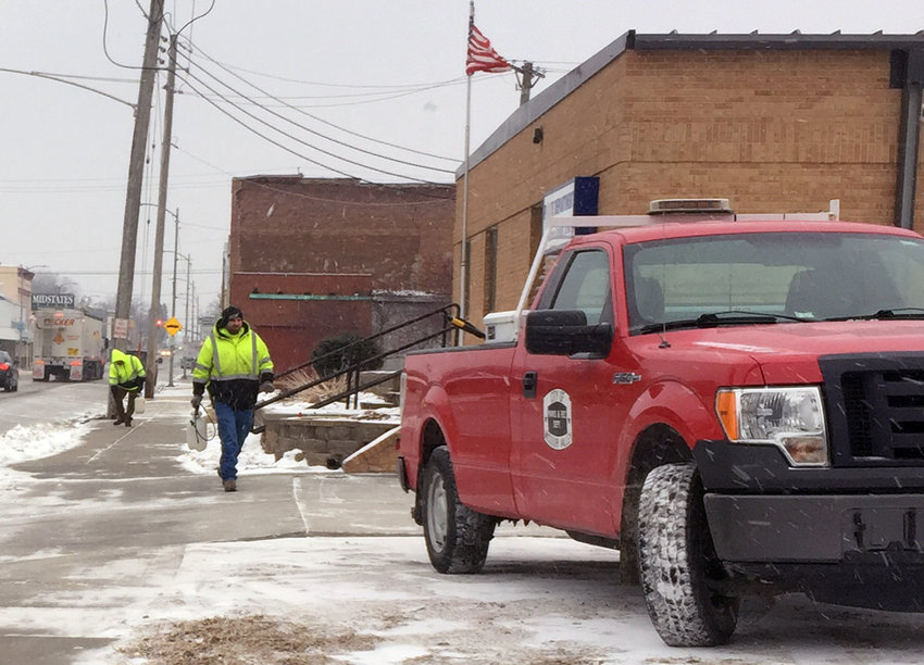 Missouri Valley Street crews prepared for the anticipated snow event early Monday morning. Here, two City employees spray an ice blocking agent on the sidewalk in front of the Missouri Valley Police Department.