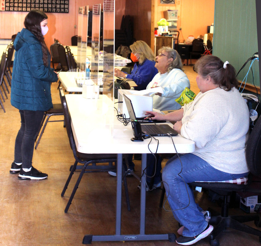 The 25th voter at the Modale Special Election on Feb. 2, Jordyn Jenkins, receives her ballot. Poll workers, from forefront, are Lynette Sell, Peggy Hill, and Sal Vittatoe.