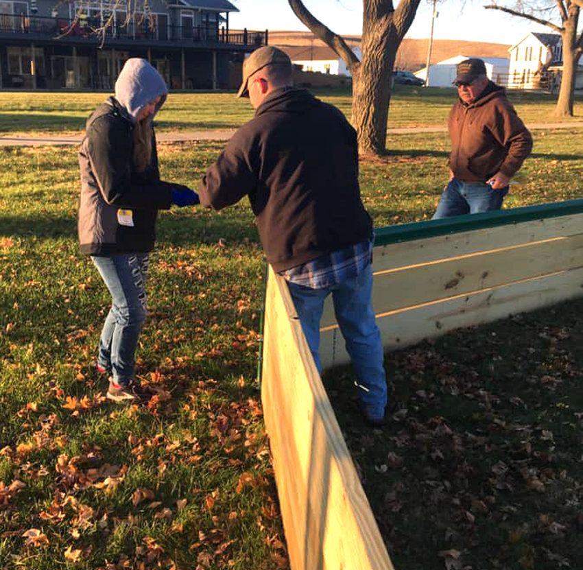 Emma Dunham, along with her father and grandfather, built Gaga Ball pits in the Dow City and Dunlap parks. Here, they are seen in the chilly morning working on the Girl Scout Gold Award project.