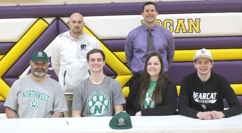 Tre Melby (front, second from left) and his family are all smiles after he signed his letter of intent to continue playing football at Northwest Missouri State starting in the fall of 2021.  He is seated with his parents, Trever Melby, Tre Melby, Tabbi Melby, and Tru Melby.  Standing in back in Lo-Ma Head Football Coach Matt Straight and Lo-Ma Activities Director Nate McDonald.  Melby signed on Feb. 3.