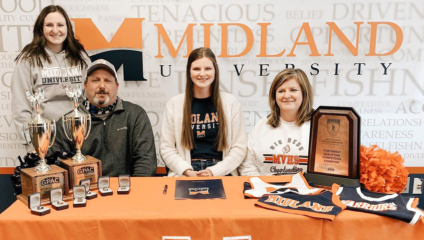 Missouri Valley senior Carsen Collins (seated, middle) is all smiles after she signed her letter of intent to continue cheering at Midland University in Fremont, Neb., in the fall of 2021.  Seated with her are her parents, Jon (left) and Leslie (right) Collins.  Standing in back is her older sister, Hannah.