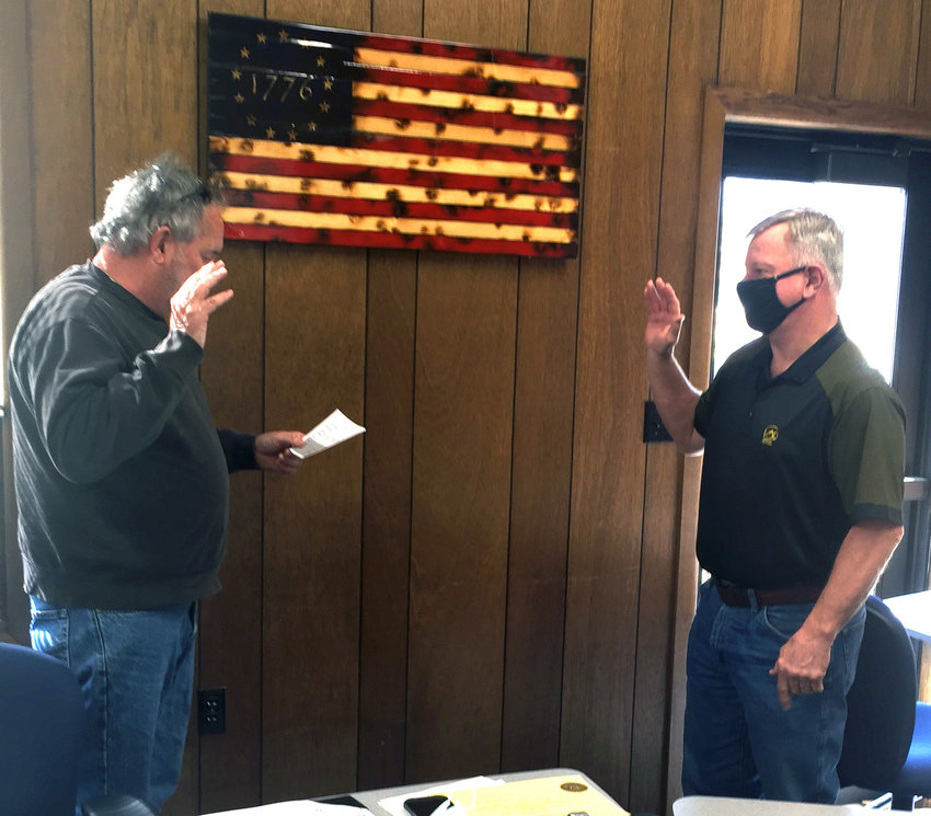 Monona County Chairman of the Board of Supervisors, Tom Brouillette, left, offers incoming Supervisor Vince Phillips the oath of office during the regular Monona County Board of Supervisors meeting on Tuesday, March 9.