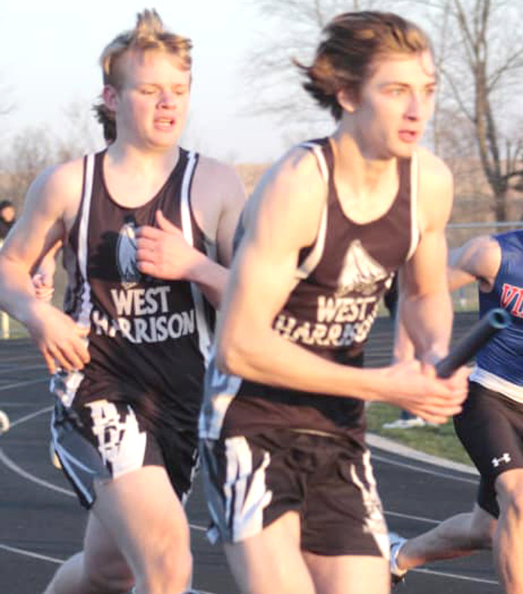 Aaron Peterson takes the baton from Gunnar Stolz in the first exchange of the 4 x 200 m relay at the Stanton Co-Ed Ralays held on April 1 in Griswold.