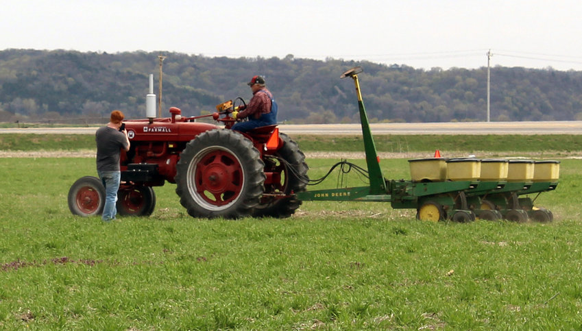 Arthur Wisecup, standing, and Brad Williams begin the process of planting corn in a Missouri Valley field. In honor of the community's 150th year, they used a 1953 Farmall to plant the field. When it is time to harvest, in September, they will use implement from the 1950s as well.