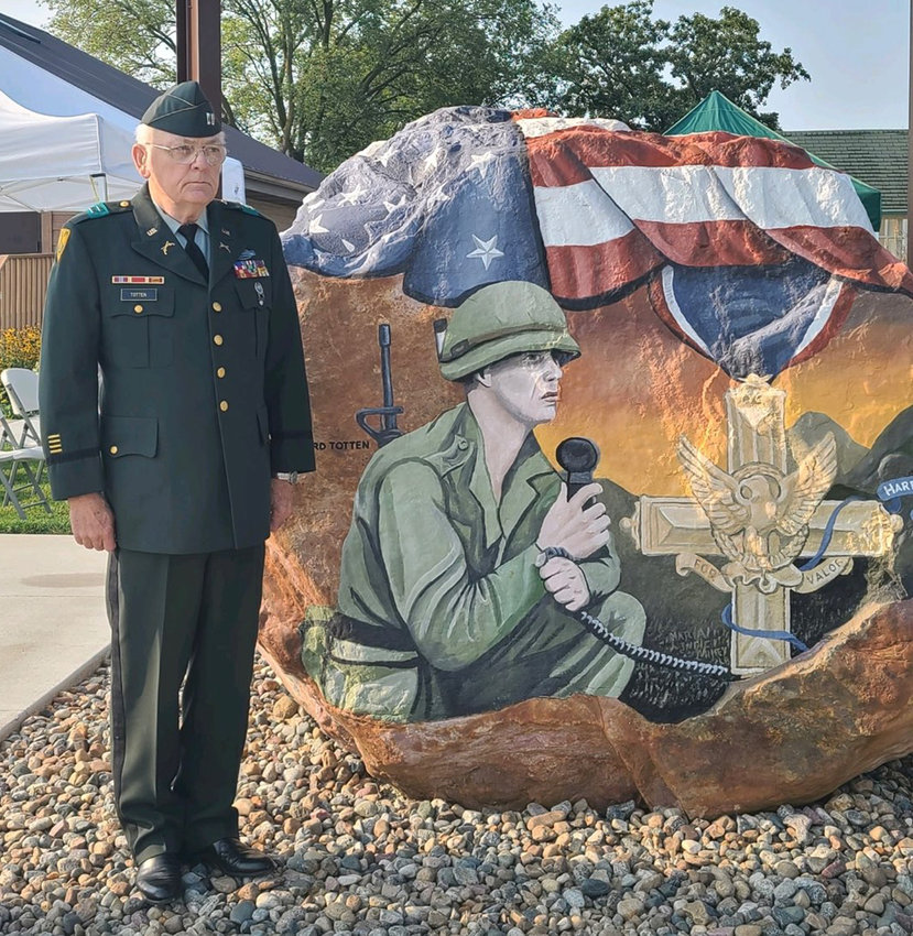 Clifford Totten stands next to Harrison County's Freedom Rock, where he is depicted.
