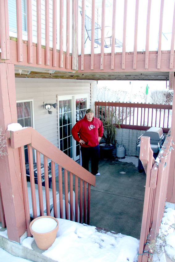 Eric Gruenhagen poses on his patio, beneath his deck. Eldridge building code forbids his plan to expand his Harvest Lane home to the same dimensions as the deck.