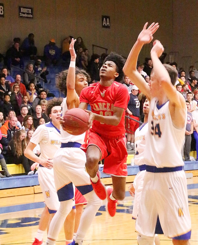 Lancer junior Tavi Seales splits a pair of Davenport North defenders on this drive down the lane.