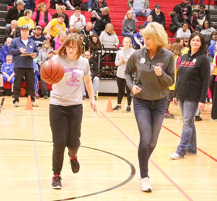 Tracy Lindaman runs alongside a competitor in the Special Olympics basketball skills competition.
