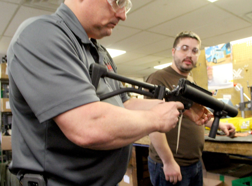 Lewis executive Don Canada displays a grenade launcher before Eldridge native Aaron Lecander installs a firing pin.