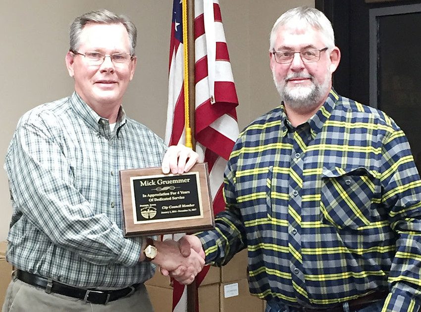 Durant city council member Mick Gruemmer (left) was presented a commemorative plaque by Mayor Scott Spengler at the Dec. 18 council meeting in honor of his four years of service to the council. Gruemmer chose not to run for re-election in November.