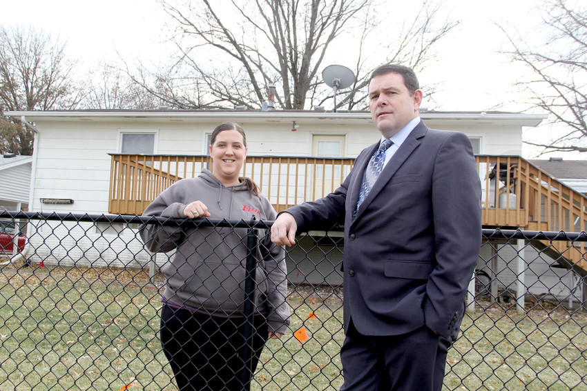 Hallie Eller and Joe Stutting pose on a strip of land that North Scott School Board members gave to Eller so she can build an addition that complies with Eldridge setback code. The 5-foot-wide strip covers a utility easement that neither Eller nor the district can build upon.