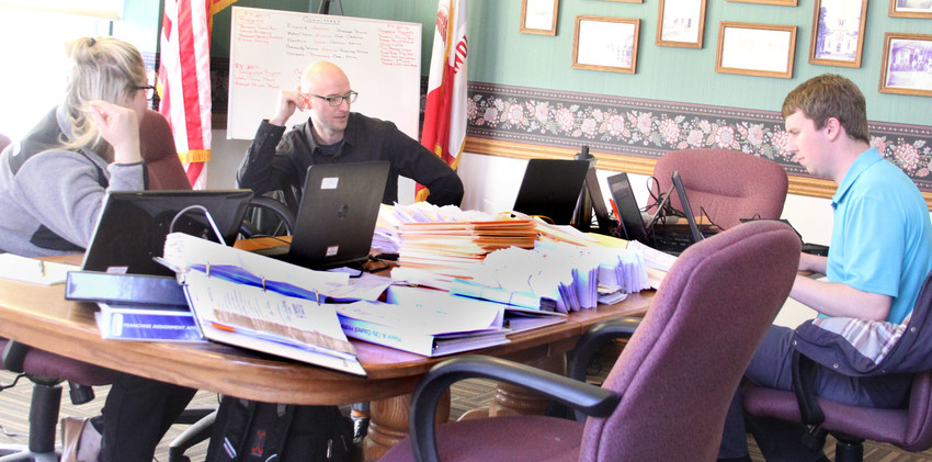 Iowa Auditor staff review city documents amassed Monday on the Long Grove City Hall council table.