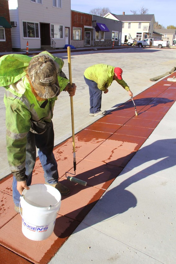 Workers seal red concrete Monday on Eldridge's Second Street.