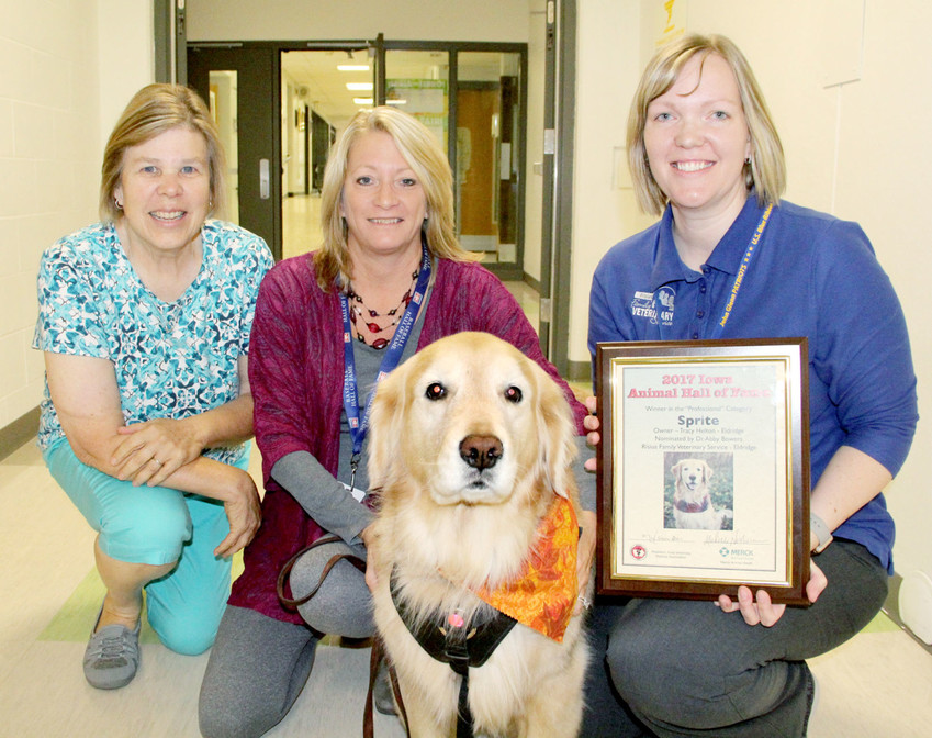 Trish Reisener, Tracy Helton and Dr. Abby Bowers, pose with Sprite, and a plaque commemorating her inclusion in the Iowa Veterinary Association Animal Hall of Fame.