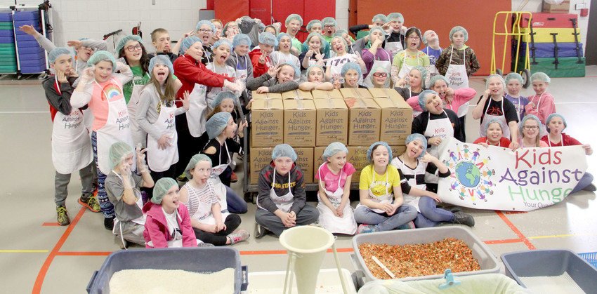 Shepard students pose with silly faces around boxes containing 5,000 meals for The Jack Project.