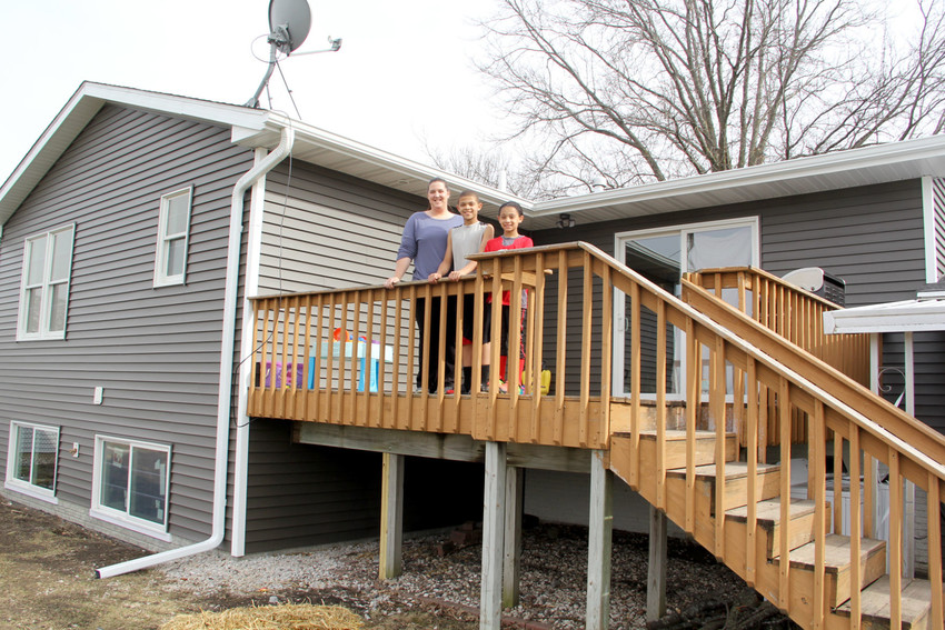 Hallie Eller, and kids, Jesse and Kamilah, pose on their old deck and their newly expanded home.