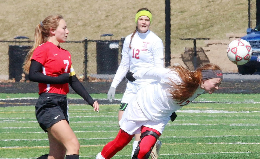 With temperatures in the 20s, and a strong wind out of the northwest Saturday morning, this header by Lancer junior Chloe Engelkes had to hurt. Also pictured is Brenna Kundel.