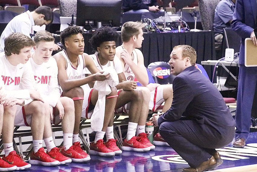 Coach Shamus Budde addresses his team prior to the game. Seated from left are Ty Anderson, Tavi Seals and Reece Sommers.