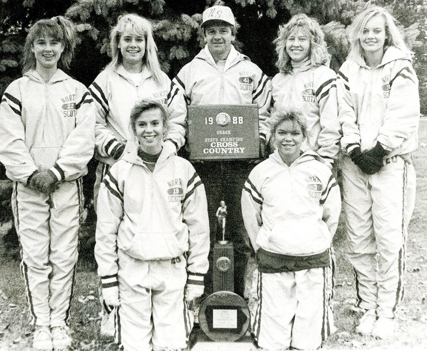 Members of the 1988 state champion cross-country team pose with coach Dennis Johnson and their trophy. Front (l-r): Deb Rosmilso and Barb Petersen. Back: Connie Moore, Christa Coe, Johnson, Chris Brehmer and Tracy Schneckloth.