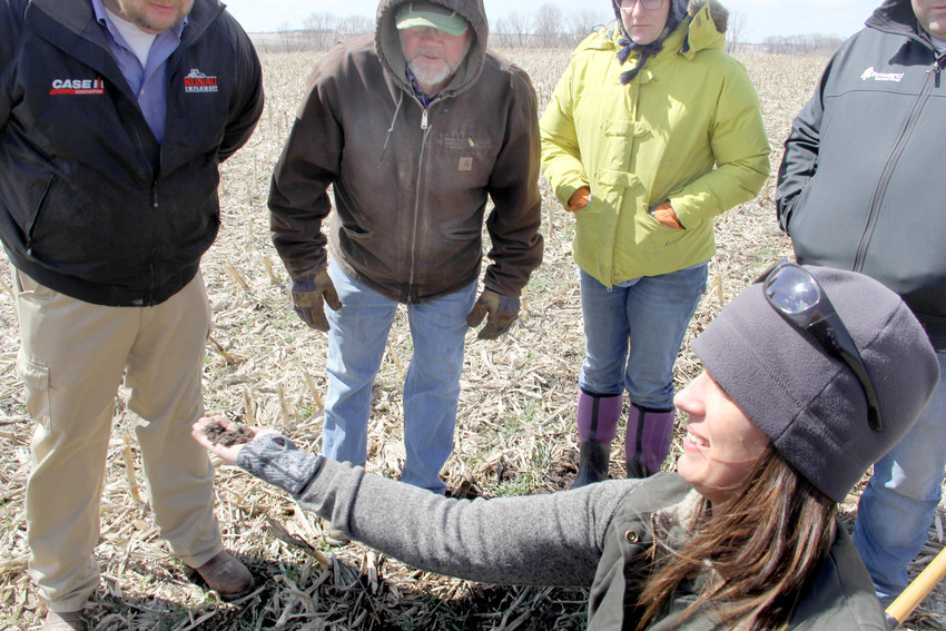 Elyssa McFarland digs a clump of cereal rye grass at the Oberbroeckling farm's cover crop field day, April 4.